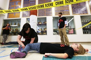 Beneath a 6-foot-tall cigarette, Grand Island Senior High student Shelby Smolinski (left) tapes an outline around fellow student Adam Lehechka as Sandy Yager of Tobacco Free Hall County tapes an outline around student Kaili Smith (lower right) under the supervision of teacher Matthew Lehechka, while preparing for Kick Butts Day. When completed, seven outlines of bodies symbolize that a person dies every seven seconds from tobacco-related illnesses worldwide. Sponsored by Tobacco Free Hall County, four area high schools, Wood River, Doniphan-Trumbull, Heartland Lutheran and Grand Island Senior High, participated in on-campus tobacco awareness activities Wednesday. (Independent/Barrett Stinson)